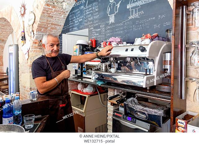 Waiter waiting at espresso machine in an old cafe in Cagliari, Sardinia,Italy