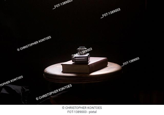 Camera and book on table against black background