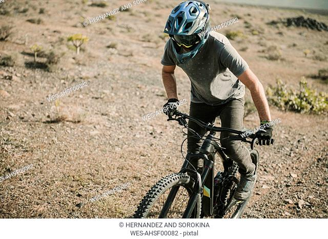 Spain, Lanzarote, mountainbiker on a trip in desertic landscape