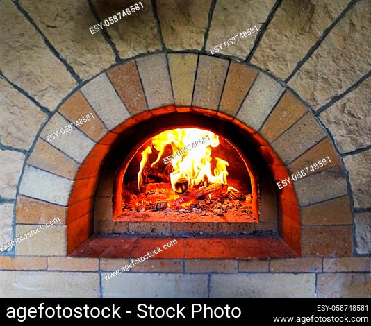 Burning firewood in traditional oven at restaurant kitchen