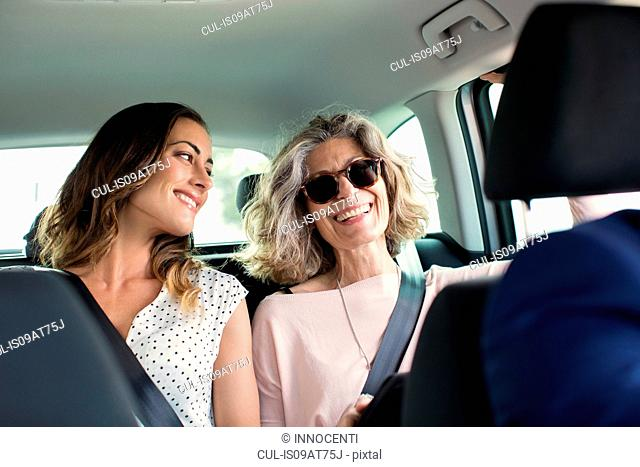 Two women chatting in back seat of car