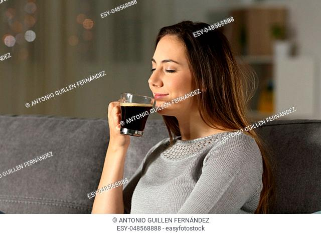Woman enjoying a cup of coffee in the night sitting on a couch in the living room at home