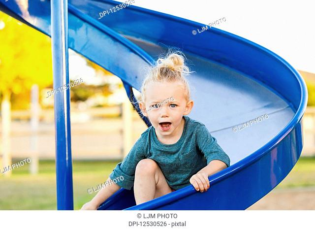 A young girl with blond hair playing in a playground and going down a slide on a warm fall day; Spruce Grove, Alberta, Canada