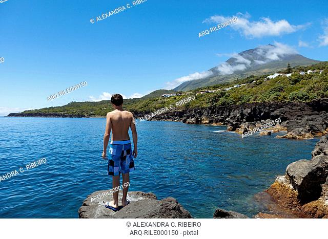 Teenager Standing By The Sea With The Highest Mountain Of Portugal In The Background