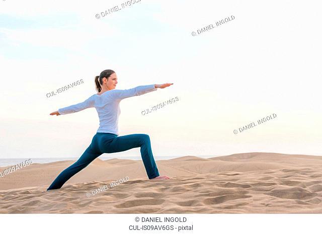 Woman practicing yoga warrior pose on dune, Maspalomas, Gran Canaria, Canary Islands, Spain