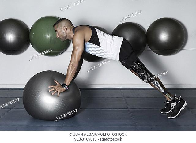 Side view of concentrated sportsman with leg limb training with medicine ball in gym