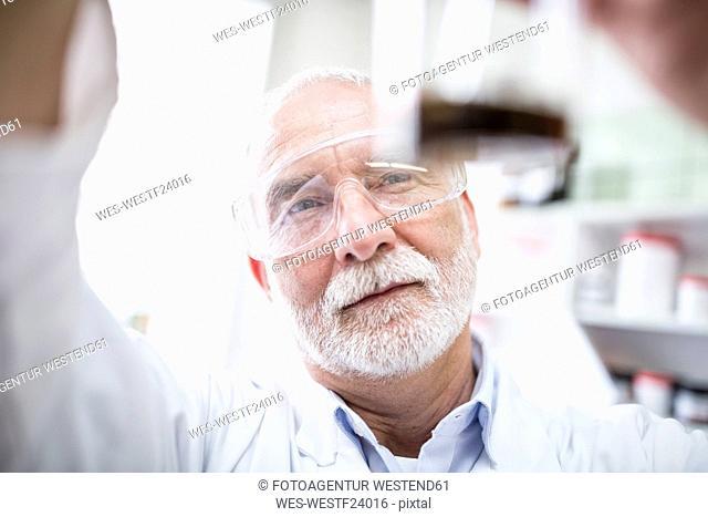 Man looking at beaker in laboratory