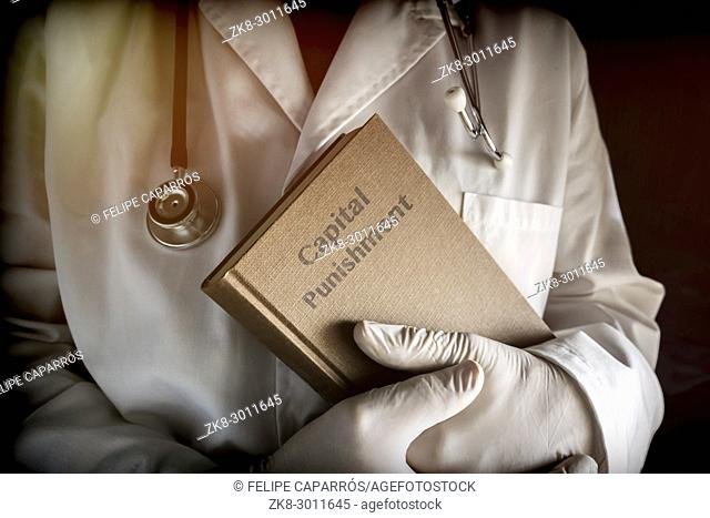 Doctor holds in a Capital Punishment book in a hospital. Conceptual image