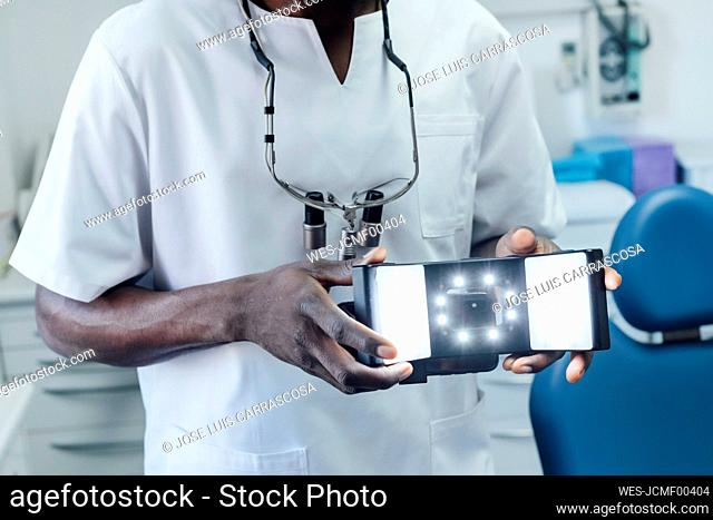 Close-up of dentist holding special photographic apparatus