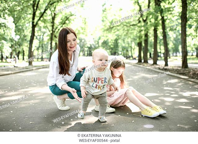 Smiling mother with her two kids in the park