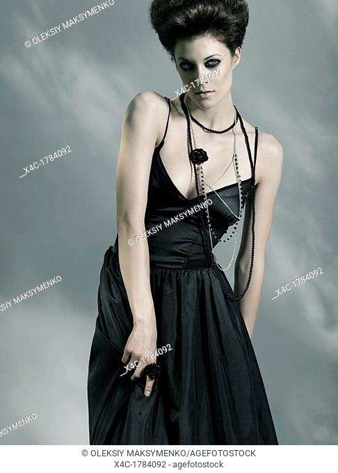 Beautiful young fashionable woman wearing long black dress isolated on gray background