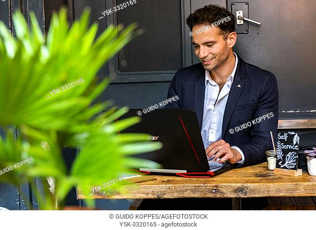 Berlin, Germany. Young Adult & Gay Professional working with his laptop computer and smartphone inside a coffee place to help out his customers with their...