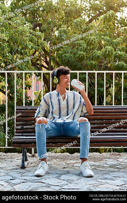 Young boy with afro hair drinks coffee while he is sitting on a bench