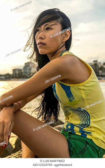 Portrait of a Chinese young woman sitting on the beach along the seaside of Sitges; Sitges, Barcelona province, Spain