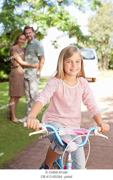 Portrait of smiling girl on bicycle with parents in background