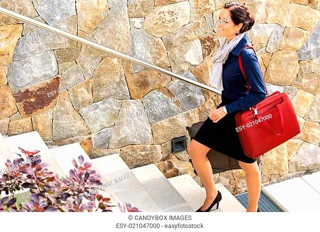 Smiling woman climbing stairs luggage traveling arriving