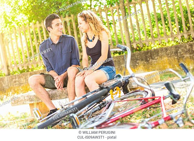 Young couple chatting on park bench, bicycles in foreground