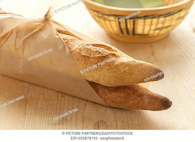 Two French baguettes parisienne wrapped in paper
