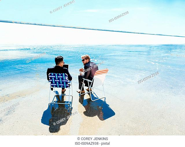 Businessmen sitting in deckchairs on Los Angeles river, California, USA