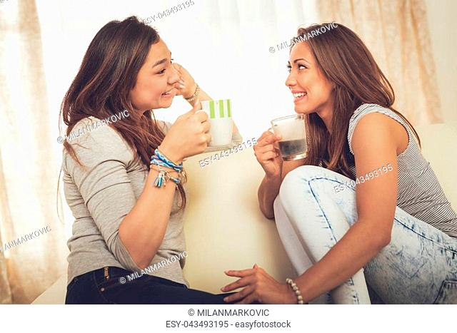 Two young cheerful female friends enjoying coffee and talking in an apartment