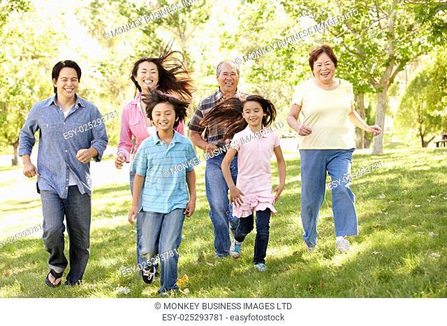 Multi-generation Asian family running in park