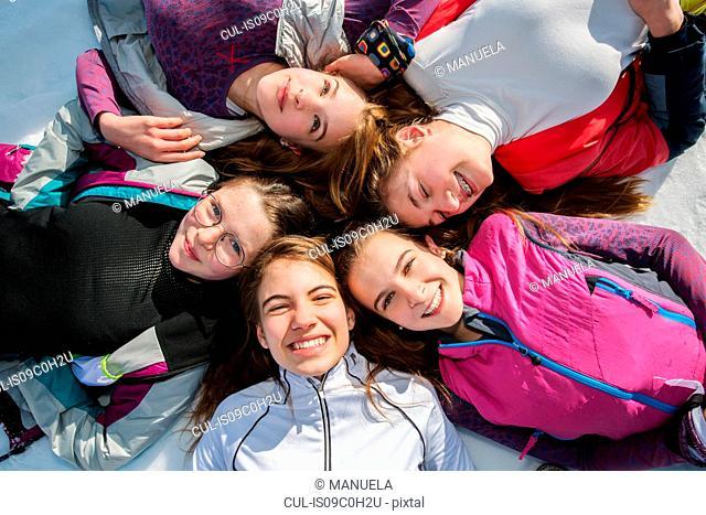 Five teenage girl skiers lying in a circle in snow, overhead portrait, Tyrol, Styria, Austria