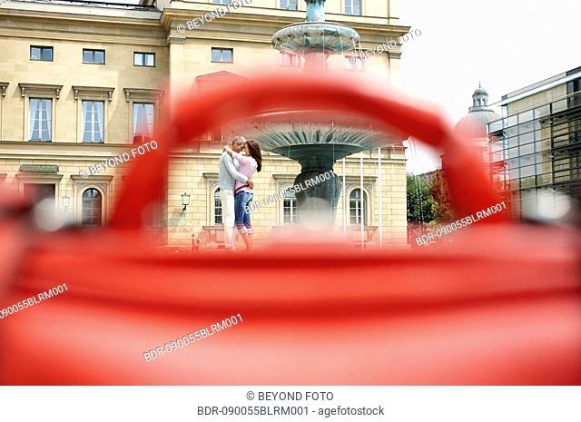 couple embracing in city seen through bag