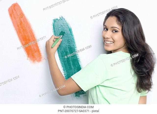 Portrait of a young woman painting the Indian flag on a wall and smiling