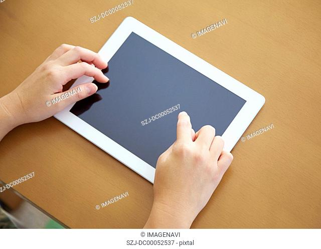 30's woman's hands touching a tablet PC