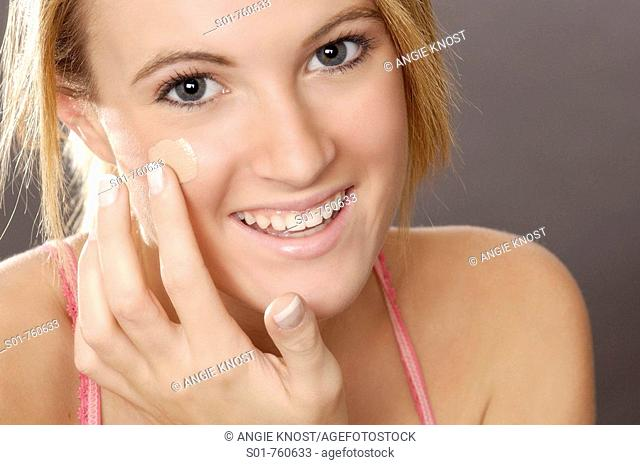 This stock photo shows a young woman in her late teens or early 20s applying foundation make-up with a neatly manicured hand  She is smiling and making eye...
