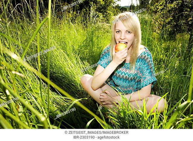 Smiling young woman sitting in tall grass eating an apple