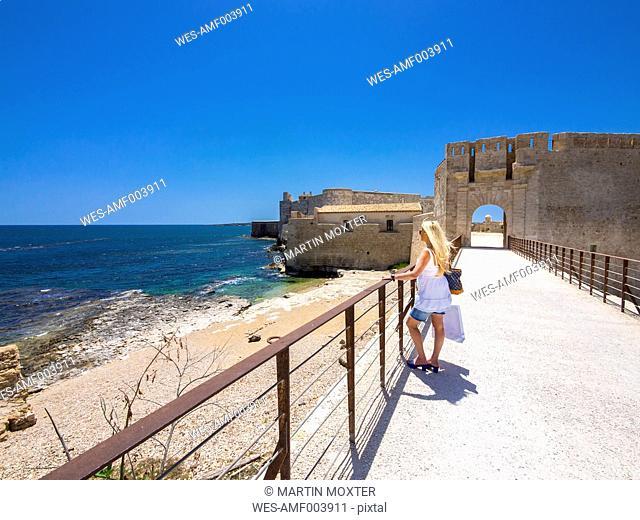 Italy, Sicily, Syracuse, Ortygia, Castello Maniace, Female tourist looking to sea