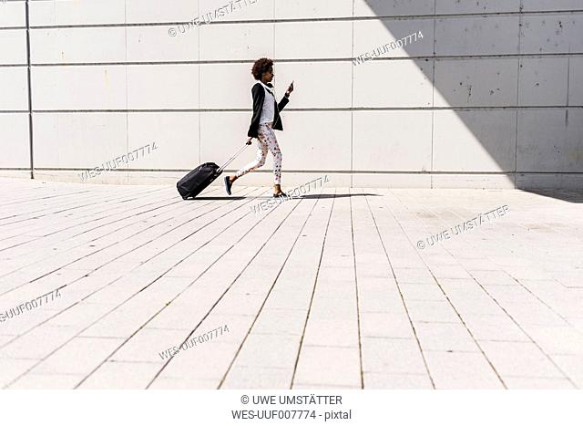 Walking businesswoman with trolley bag looking at her smartphone