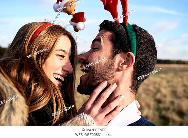 Happy carefree couple wearing Christmassy headdress in the countryside