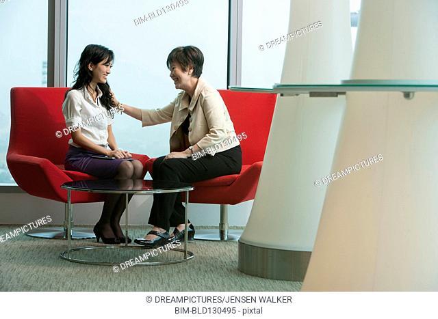 Businesswomen talking in office lobby area