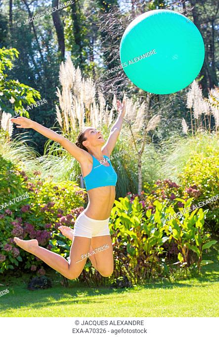 happy young woman trains with exercise ball outdoor in park, jumping