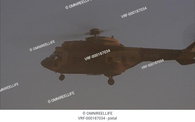 Military helicopter with camouflage pattern in sky