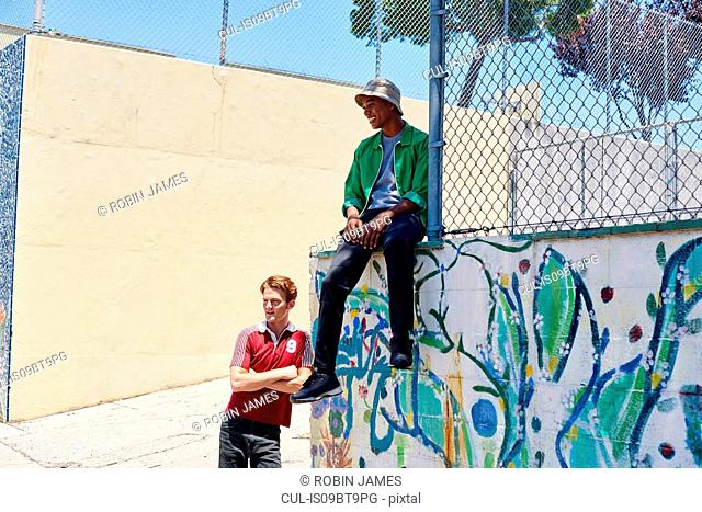 Two young men waiting by park fence, Los Angeles, California, USA