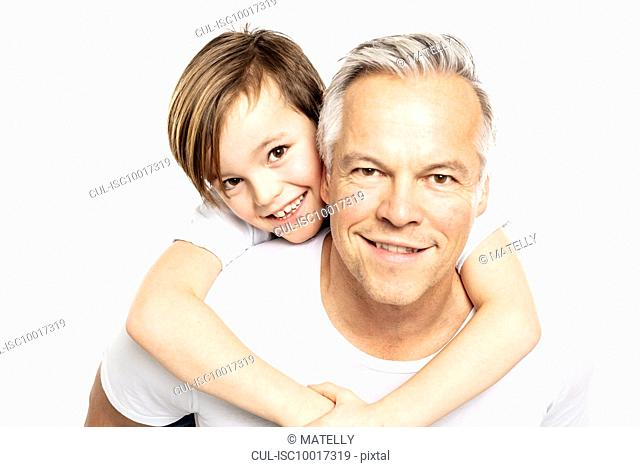 Father giving son piggyback ride, white background