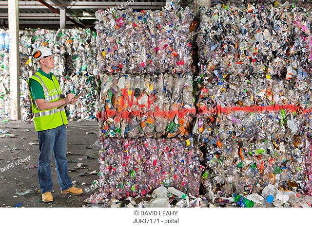 Worker examining bales of recycled plastic in recycling plant