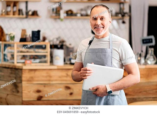 Modern worker. Positive and confident male cafe worker in apron holding a tablet and smiling at a camera, standing in a cafe