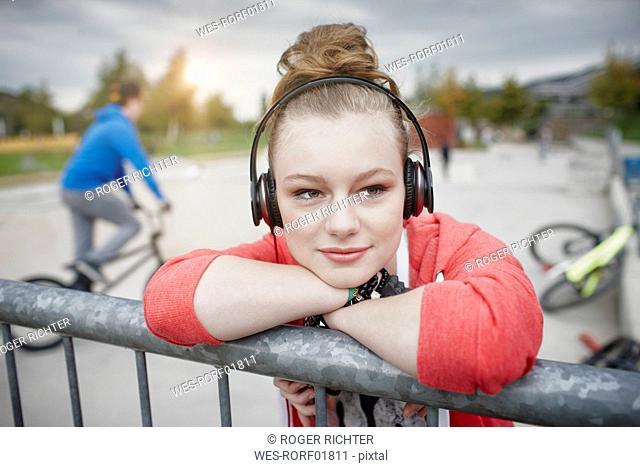 Portrait of teenage girl wearing headphones at a skatepark