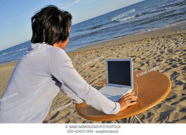 Wman (43) on laptop by beach, Provence, France