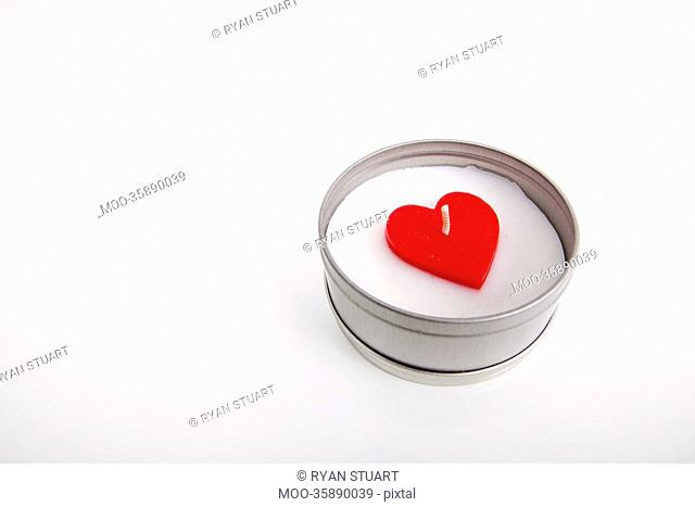 Red and white candle with heart shape in container against white background