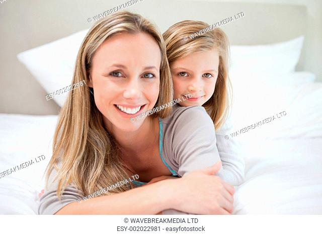 Little girl lying on her mothers back