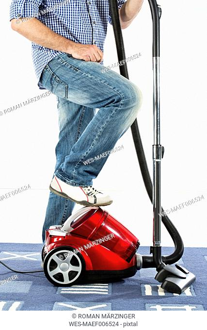 Mature man standing with vaccuum cleaner