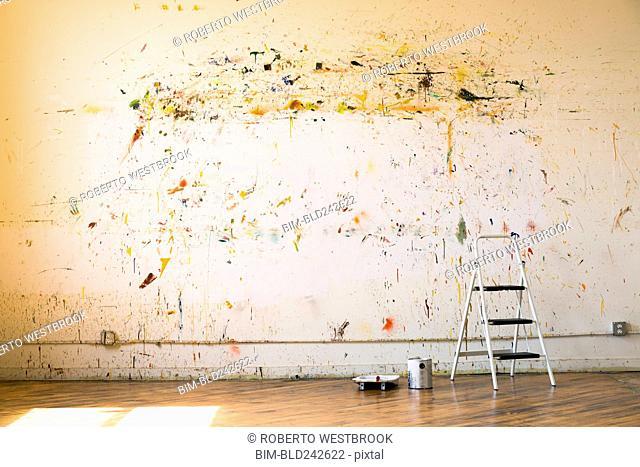 Paint splattered on wall near ladder