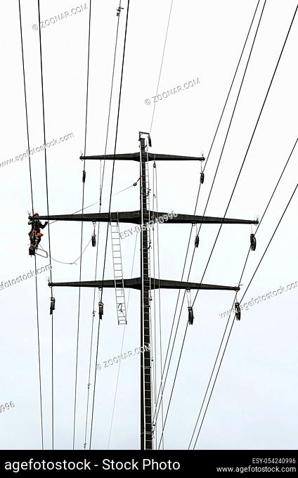 Working professional men on high voltage power lines high up on lattice crosses doing dangerous electrical work
