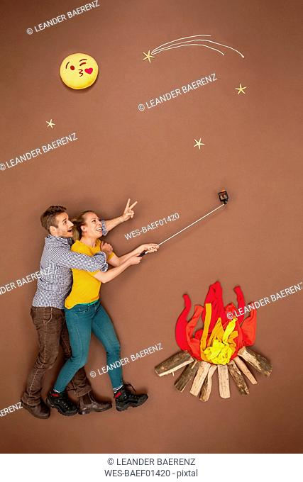 Couple roasting sausages at the campfire and taking a selfie