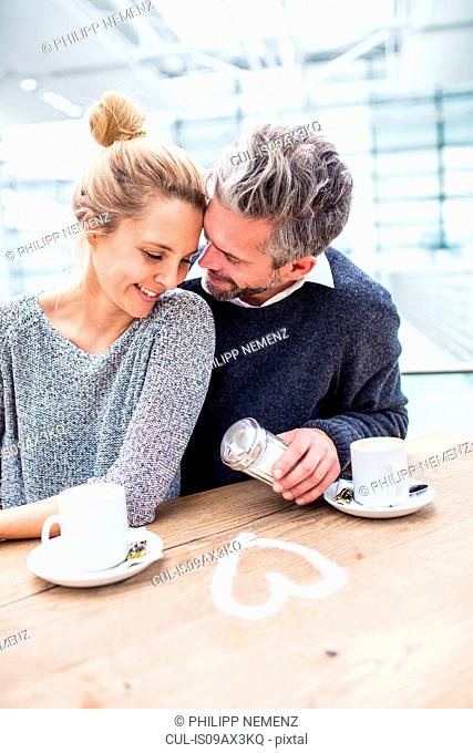 Couple sitting together, drinking coffee, heart shape made from sugar on table in front of them